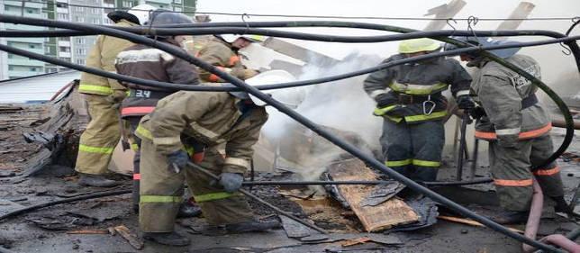 Баграми растаскиваются горящие деревянные материалы